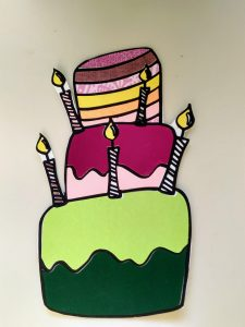 Birthday cake embellishment made by coloring with paper